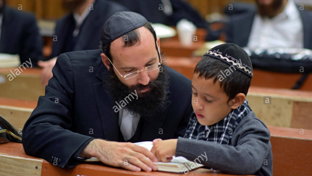 religious-jewish-father-and-child-studying-in-the-synagogue-in-brooklyn-ED3BJ1